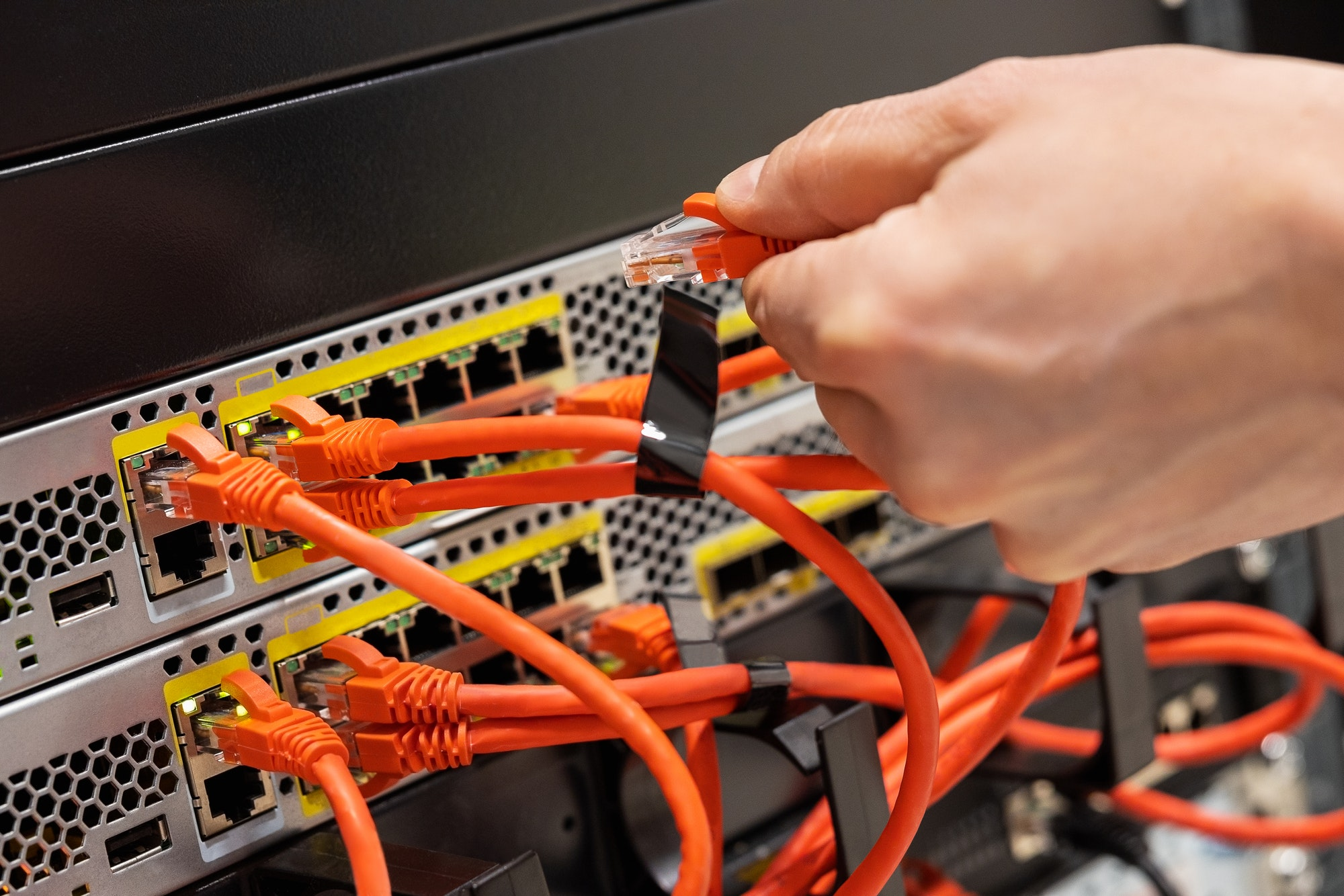 Male IT Engineer Plugging Network Cable In Router in Datacenter